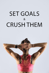 "Back view of beautiful young person wearing red sportswear bra on grey background. Athletic model girl wearing smartwatch posing with hands behind head. Motivational phrase ""Set goals and crush them"""