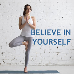 "Beautiful smiling happy young woman working out indoors, doing yoga exercise on blue mat, standing in Vrksasana Posture, Tree Pose, full length. Motivational phrase ""Believe in yourself"""