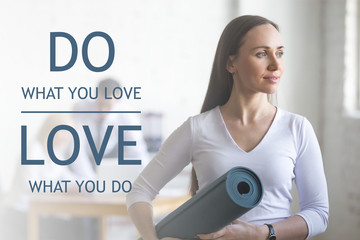 "Business and healthy lifestyle concept. Portrait of beautiful sporty young office woman standing with yoga mat at workplace on break time. Motivational text ""Do what you love, love what you do"""