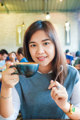 Asian woman drinking hot latte coffee at cafe