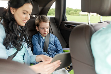 happy family with tablet pc driving in car
