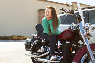 Young attractive woman with long curly hair wearing green sweater and jeans is sitting on red motorcycle and looking aside on the road seriously on summer day outdoor. Lifestyle, vacation