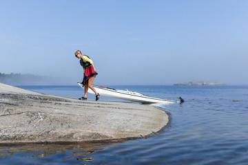 Woman pulling canoe on coast, Sweden