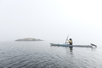 Woman paddling in fog, Sweden
