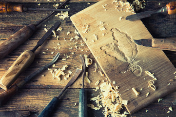 Chisels and carved piece of wood in traditional carpenter workshop