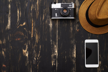 Top view of hat, old-fashioned camera and smartphone on wooden t