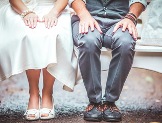 Bride and groom in boho clothes on the bench. Only legs