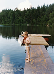 Boy in underwear standing on jetty looking inside fishing rod