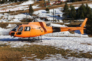 Orange rescue helicopter parked in the snowy mountains