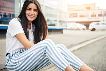 Beautiful woman wearing striped pants smiles