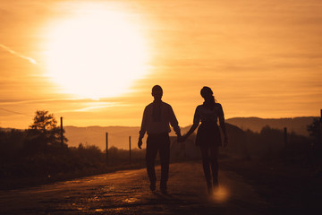 Warm picture of young couple holding each other hands during eve