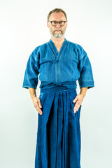 Kendoka - Man in kendo clothes, hakama and jacket. Studio shot on white background.