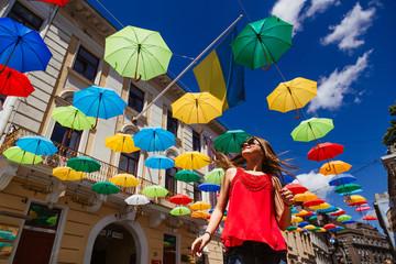 Bright colored umbrellas hang over the pretty girl in foxy sungl