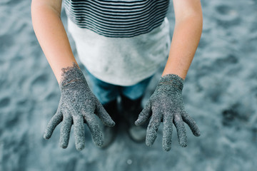 Childs hands outstretched covered in sand