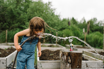 Young girl drinking water from a hose