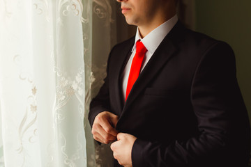 Man buttons up his black jacket while standing before the window