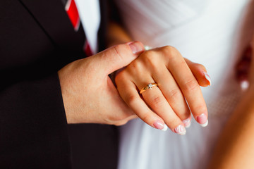 Man holds tender bride's hand with french nails