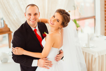 Bride looks over her shoulder while standing in the hugs of hand