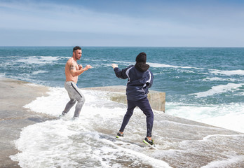 trainer and the pupil engaged on karate near the sea