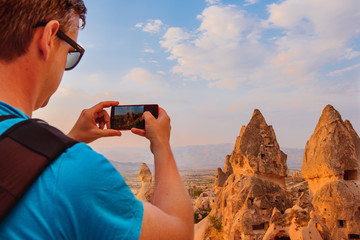 Tourist taking photos of a  landscape  in Cappadocia