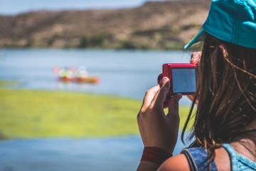 chica tomando fotografía a una piragua del río