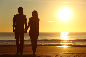 Couple silhouette walking together on the beach