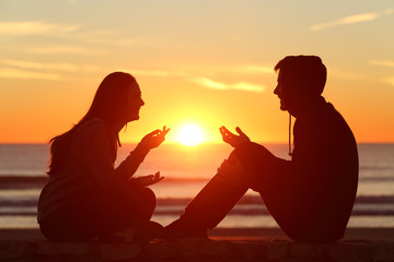 Friends or couple of teens talking at sunset
