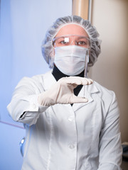 Adult woman closeup protective glasses and medical mask holding in his hand glass syringe with a needle