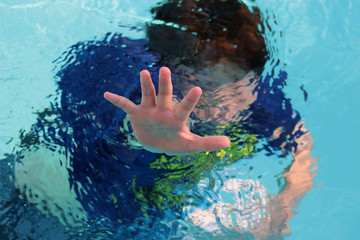 Boy drowning in pool reaches out with hand. Fototapete