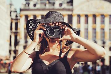 jolie femme brune style années 1960 avec chapeau de soleil et appareil photo vintage