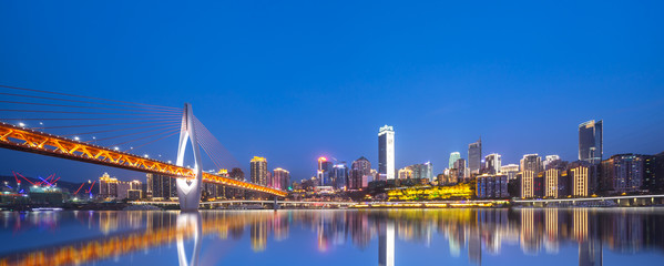 cityscape and skyline of chongqing from water at night