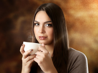 Portrait of pretty woman drinking coffee on blurred background