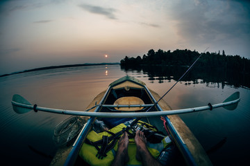 Fisherman in hipster canoes in the lake sunset. Fisheye photo. Foot Photo