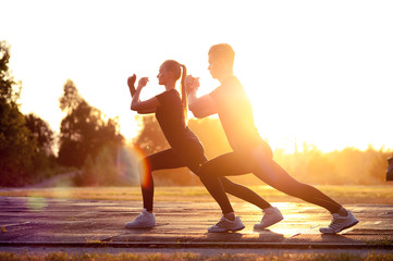 Silhouettes of fit man and woman doing lunges