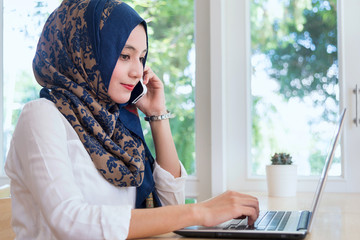 Muslim woman working on computer and talk mobile phone.