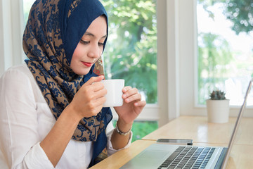 Muslim woman with computer on table , holding a coffee cup.