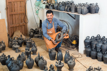 Cheerful male artisan with ceramic vases