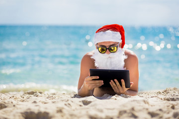 Santa Claus on the beach with a tablet in hands
