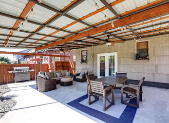 Covered back deck with concrete floor and outdoor furniture.