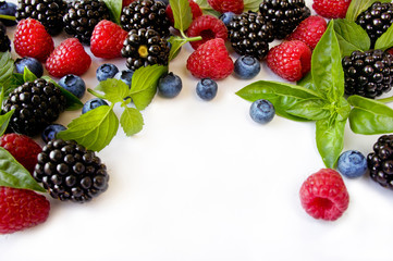 Various fresh summer berries. Ripe blueberries, raspberries and blackberries. Berries on white background. Top view with copy space.
