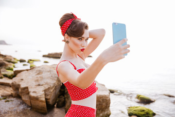 Sexy pin up girl in swimsuit making selfie with smartphone