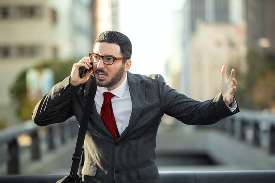 Angry furious businessman on cell phone call yelling and screaming in city