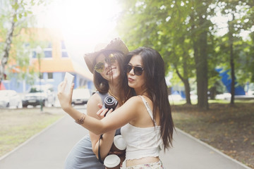 Girls friends taking selfie photos with smartphone outdoors