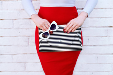 Fashionable woman in red skirt with striped clutch Wall mural