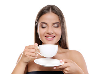 Beautiful young woman with cup of coffee on white background