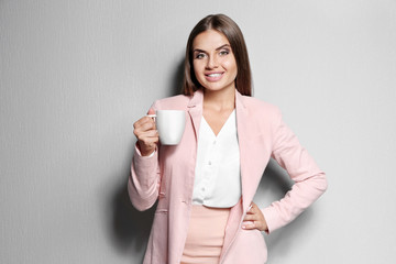 Beautiful young woman with cup of coffee on color background