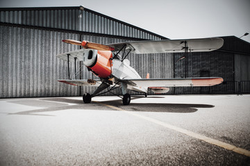 Vintage old plane in front of the hangar. Copyspace on the ground.