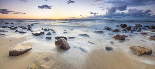 Zachód słońca nad bałtycką plażą,głazy piastowskie na wyspie Wolin