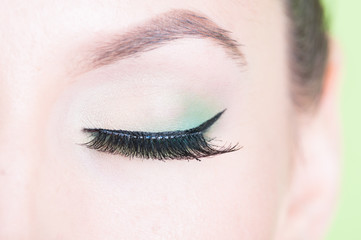 Close-up of professional green eye make-up