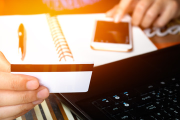 Online payment, man's hands holding a credit card over laptop an
